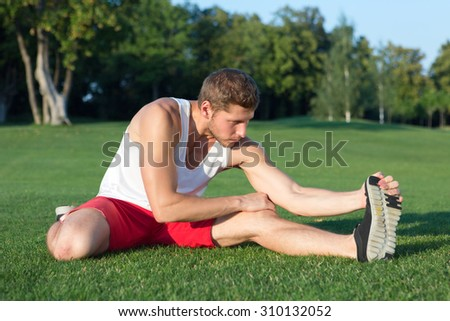 Sport and health concepts. Close-up picture of sportsman stretching his leg outdors. Man in red shorts training before jogging in the park. - stock photo