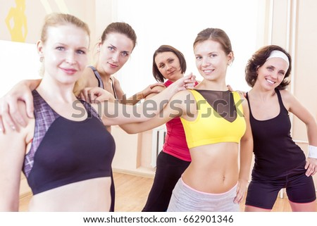 Sport and Healthy Lifestyle Concepts. Closeup Portrait of Five Happy Caucasian Female Athletes Posing Together Embraced Against Fitballs in Gym.Horizontal Image