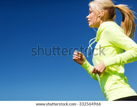sport and lifestyle concept - woman doing running with earphones outdoors - stock photo