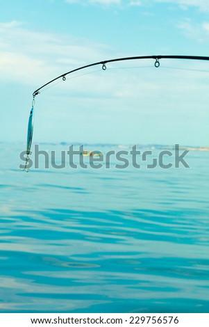 Sport and recreation. Fishing bait - rod with wobbler against the blue sea water surface - stock photo