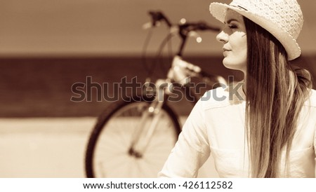 Sport and recreation. Young girl in straw hat resting after cycling on beach. Smiling tourist spending time on seaside. Leisure in summer. - stock photo