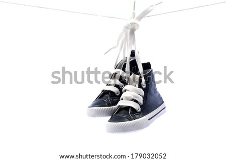 Sport baby shoes hanging on the rope  - stock photo
