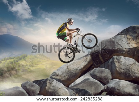 Sport background. Cyclist climbing on a rock.  - stock photo