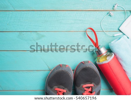 Sport background,running shoes and fitness accessories on wood,top view