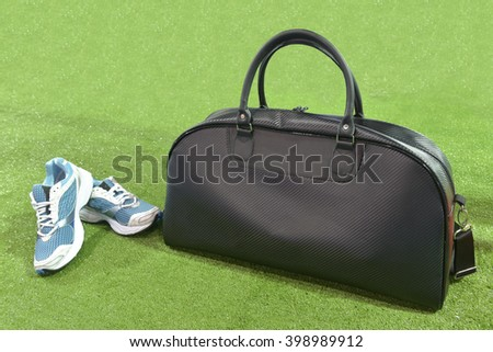 Sport bag black color, Picture of a pair of blue trainers over a green grass background. - stock photo