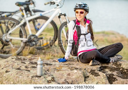 Sport bike woman sitting on a mountain next to bike relaxing and enjoying nature - stock photo