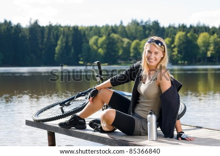 Sport biking young woman sitting on pier by natural lake