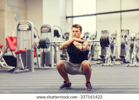 sport, bodybuilding, lifestyle and people concept - young man with barbell doing squats in gym - stock photo
