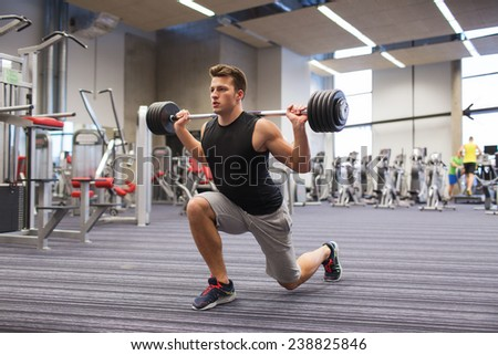 sport, bodybuilding, lifestyle and people concept - young man with barbell flexing muscles and making shoulder press lunge in gym - stock photo