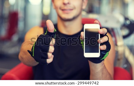 sport, bodybuilding, lifestyle, technology and people concept - happy young man with smartphone showing thumbs up in gym - stock photo