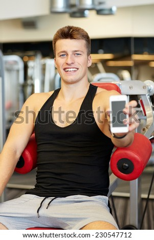 sport, bodybuilding, lifestyle, technology and people concept - smiling young man showing smartphone blank screen in gym