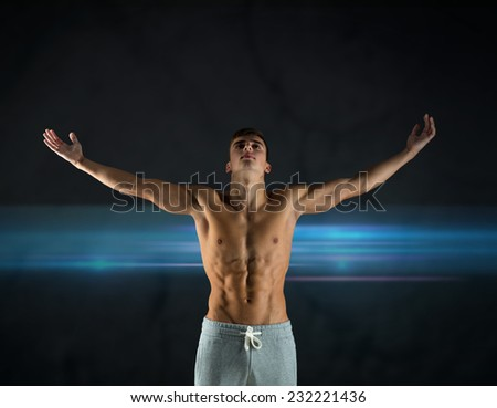 sport, bodybuilding, strength and people concept - young man standing with raised hands over dark background - stock photo
