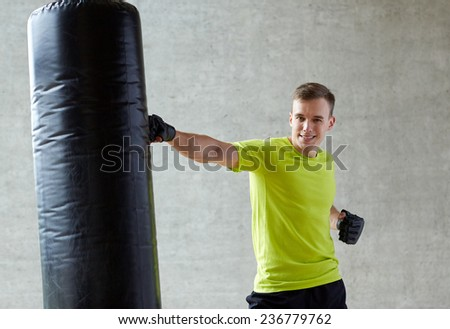 sport, box and people concept - smiling young man in gloves boxing with punching bag in gym - stock photo