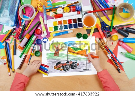 sport car racing child drawing, top view hands with pencil painting picture on paper, artwork workplace - stock photo