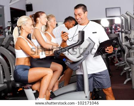 sport coach timing cyclist on gym bike - stock photo