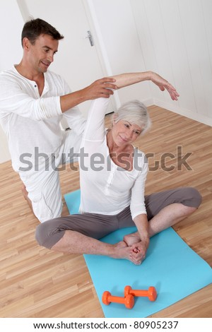 Sport coach training senior woman with stretching exercises - stock photo