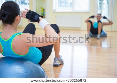 sport concept - young sporty woman doing exercises on bosu ball in gym - stock photo