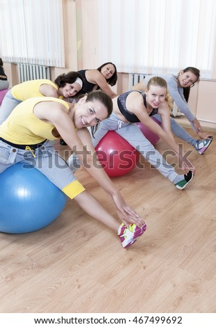 Sport Concepts. Group of Five Female Sportswomen Having Hand Stretching Exercises With Fitballs In Class.Vertical Shot