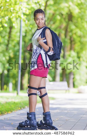 Sport Concepts. Young African American Teenage Girl Posing on Roller Skates Outdoor in Park Area. Vertical Image