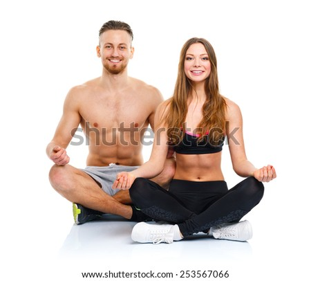 Sport couple - man and woman after fitness exercise sitting with dumbbells on the white background