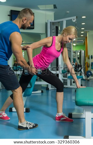 Sport couple on training in the gym. Healthy life. Help and support when performing exercises. Photos for sporting magazines and websites.