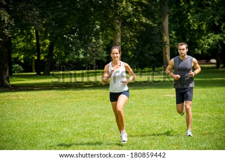 Sport couple - young man and woman jogging outdoor in nature - stock photo