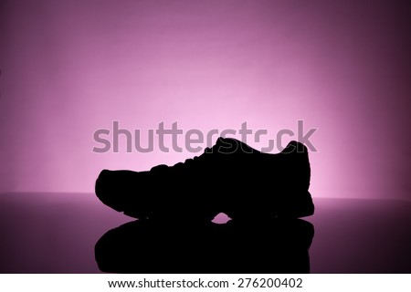 Sport equipment. silhouette of Sneakers on a pink background - stock photo
