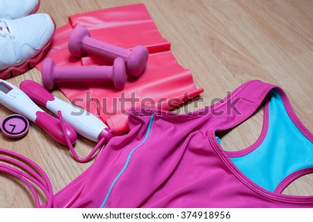 Sport equipment. Sneakers, watch, dumbbells, T-shirt, skipping rope and resistance band on wooden background.