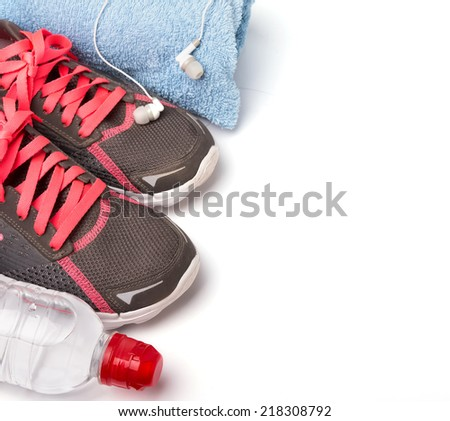 Sport equipment. Sneakers, water and earphones isolated on white background - stock photo