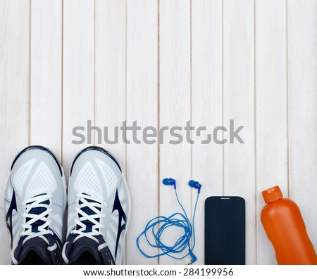 Sport equipment. Sneakers, water, earphones and phone on wooden  - stock photo