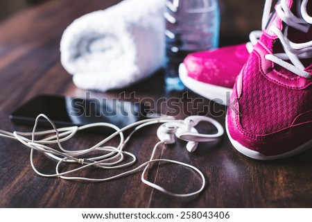 Sport equipment. Sneakers, water, towel, earphones and phone on wooden background. Focus is only on the sneakers. - stock photo