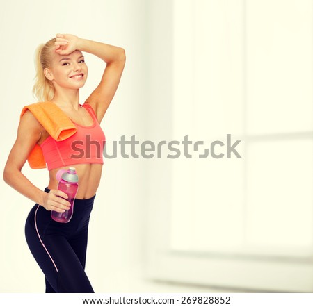 sport, exercise and healthcare - smiling sporty woman with orange towel and water bottle - stock photo