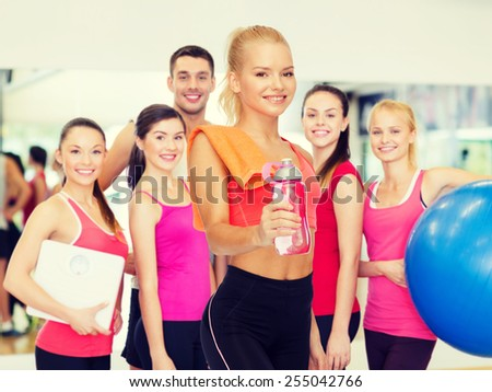 sport, exercise and healthcare - sporty woman with orange towel and water bottle - stock photo