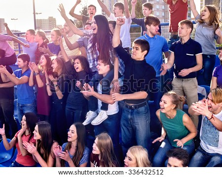 Sport fans clapping and singing on tribunes. Very big Group people. - stock photo
