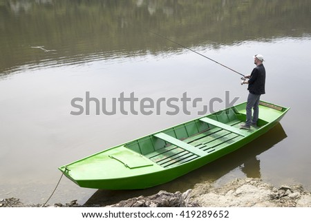 Sport Fisherman Holding Fishing Rod And Fishing From The Green Boat - stock photo
