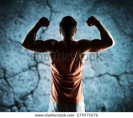 sport, fitness, bodybuilding, strength and people concept - young man or bodybuilder showing biceps over concrete wall background from back - stock photo