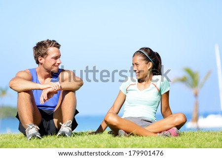Sport fitness couple relaxing after training outdoor. Young people talking sitting in grass after running and training exercise outside in summer. Caucasian man sports model and Asian woman model. - stock photo