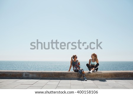 Sport fitness healthy girls relaxing after training outdoor. Young couple talking sitting in waterfront after running and training exercise outside in summer. Caucasian and asian sports women models. - stock photo