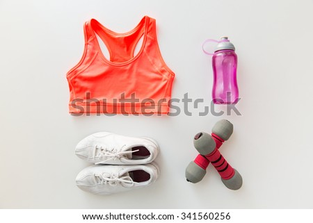 sport, fitness, healthy lifestyle and objects concept - close up of female sports clothing, dumbbells and bottle set - stock photo