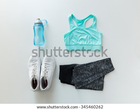 sport, fitness, healthy lifestyle and objects concept - close up of female sports clothing and bottle set - stock photo