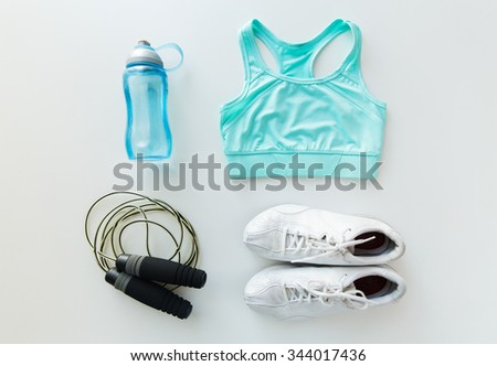 sport, fitness, healthy lifestyle, cardio training and objects concept - close up of female sports clothing, skipping rope and bottle set - stock photo