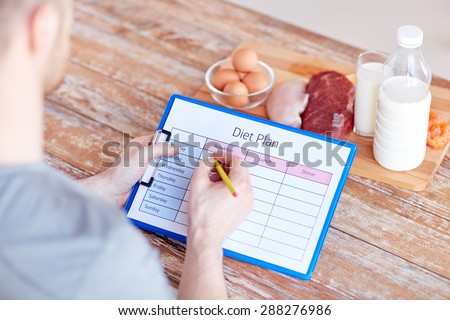 sport, fitness, healthy lifestyle, diet and people concept - close up of male hands with food rich in protein on cutting board on table - stock photo