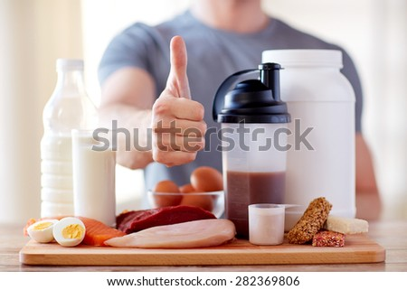 sport, fitness, healthy lifestyle, diet and people concept - close up of man with food rich in protein showing thumbs up - stock photo