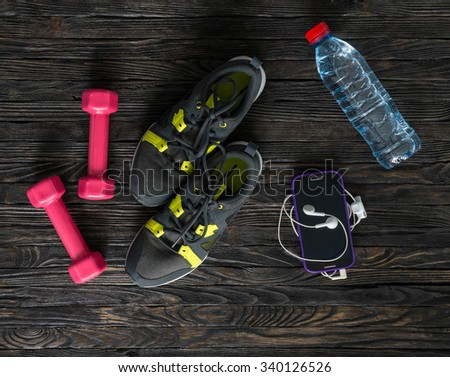 sport fitness items on dark wooden background with empty text space - stock photo