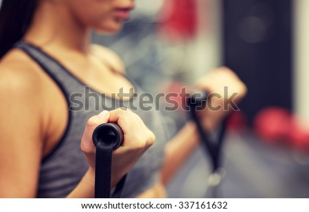 sport, fitness, lifestyle and people concept - close up of young woman flexing muscles on cable gym machine - stock photo