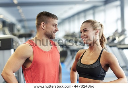sport, fitness, lifestyle and people concept - smiling man and woman talking in gym - stock photo