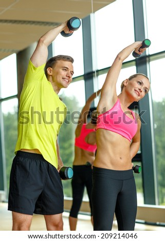 sport, fitness, lifestyle and people concept - smiling man and woman with dumbbells exercising in gym - stock photo