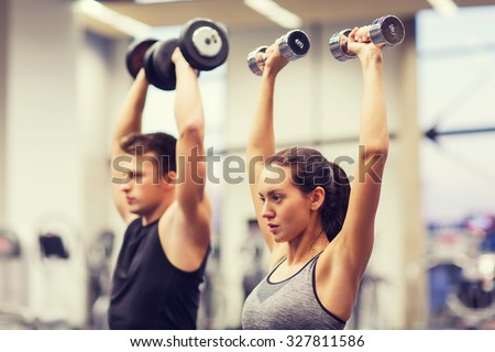 sport, fitness, lifestyle and people concept - smiling man and woman with dumbbells flexing muscles in gym - stock photo
