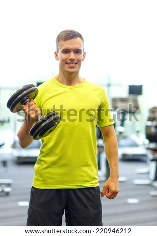 sport, fitness, lifestyle and people concept - smiling man with dumbbell in gym - stock photo