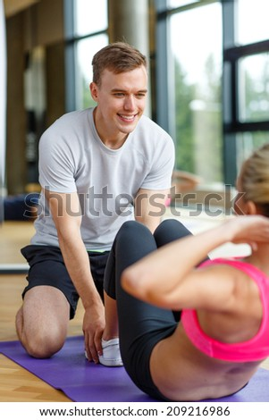 sport, fitness, lifestyle and people concept - smiling woman with male personal trainer exercising in gym - stock photo